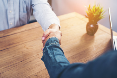 Casual business people shake hands after successful business negotiations. Banque d'images