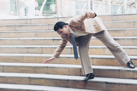 Businessman falling down the steps of staircase  Stock Photo