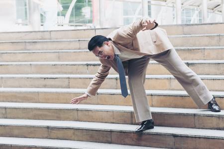 Homme d'affaires tombant sur les marches de l'escalier