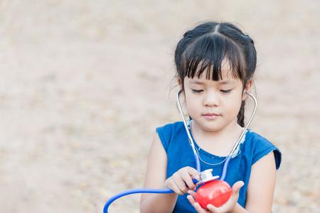자식 의사 또는 간호사 재생입니다. 행복한 여자 장난감 청진기를 수신 대기합니다.