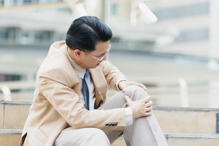 Businessman have the pain and painful knee expression and sit down on the stairs during go to office,office syndrome concept