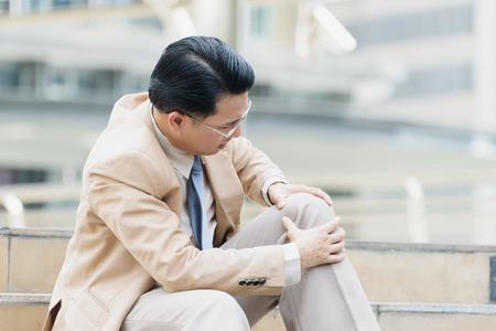 De zakenman heeft de pijn en de pijnlijke knieuitdrukking en gaat zitten op de treden tijdens naar het concept van het bureau, bureausyndroom gaan