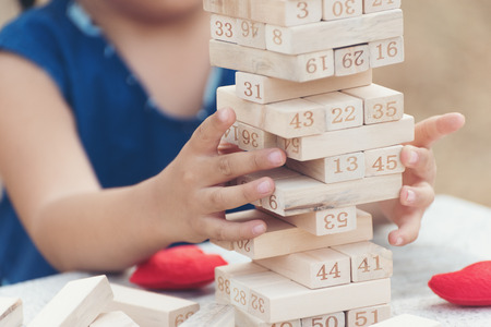 Girl kid playing stacking wood blocks for meditation practice. Hand movement control Building Computational Skills