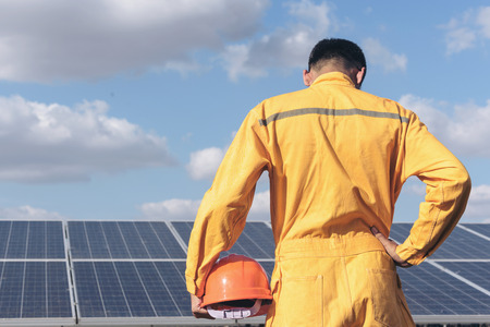 lifevest: Engineers holding a helmet with on field of photovoltaic solar panels. Renewable energy, technology of electricity concept