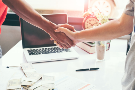 Two business man handshake ,a clock a laptop and money on the table  in the background. Stock Photo