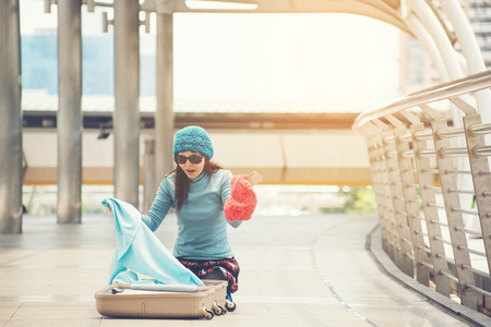 Young woman sitting in airport, looking for something in luggage, forgotten or stolen.Before boarding a flight Stock Photo