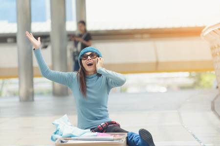 Young woman sitting in the airport, looking for something in luggage, forgotten or stolen.Before boarding a flight and using phone to and use the phone to ask for help. Stock Photo