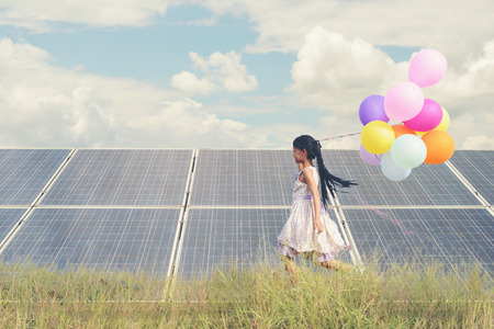 A funny girl carrying a colorful balloon running in a meadow with a Solar panel, photovoltaic. Concept of Eco-Friendly ,Clean Energy , Pure energy and Sustainable energy Stockfoto