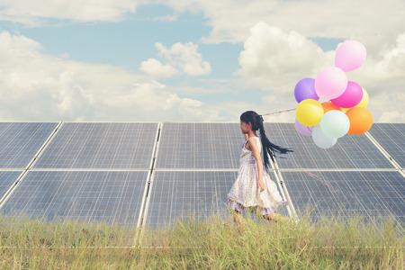 Una ragazza divertente che trasporta un palloncino colorato che corre in un prato con un pannello solare, fotovoltaico. Concetto di energia ecologica, pulita, energia pura ed energia sostenibile