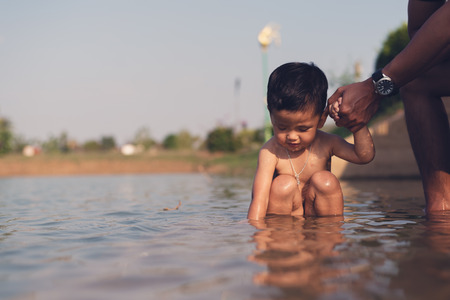 Asian kid play in water at summer, father and son holding hands while swimming in the river Banque d'images