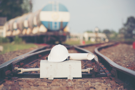 White helmet With the project plan  on the railroad tracks  with container trains on railways track in logistic station background. Banque d'images