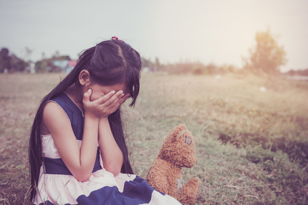 Adorable sad girl sitting alone with a teddy bear, .Upset and lonely child.Family issues concept