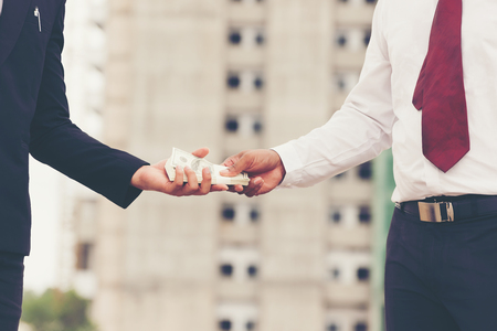 Businessman giving money to engineer  with building background,Real estate business concept