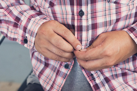 Worker Tucking His Shirt Buttons, getting ready for work day, worker and labor concept
