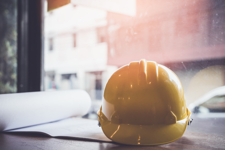 A yellow hard hat on the desk of an engineer.Protective equipment worn to protect the head from dangers of working in a construction site. The concept of Industrial construction and safety. Banque d'images