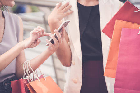 Women with the joy of shopping is using the phone during the shopping and holding shopping bags in hands,online shopping,social media concept.