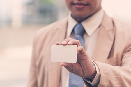 Asian businessman wearing a suit and holding business card with copy space for your text or information content,business concept Banque d'images