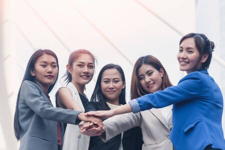 Group of business women holding hands support team. Coordinating of business unity in order to succeed in business,cooperation and teamwork business concept Banque d'images