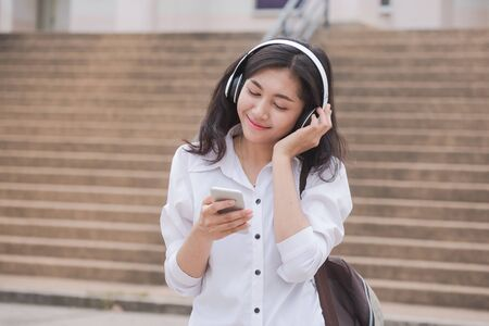 Asian girl student watching media content on smartphones and listening on line with wireless headphones,learn english, online education concept.