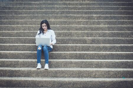 Asian woman using a tablet watching media content in online learning or communicating via social media to research for education ,sitting on the stairs in college, The concept of education and learning on line.