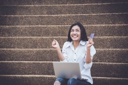 Asian women using laptops for e-commerce trading  or purchase courses online via the Internet with credit card. online learning  and  business concept