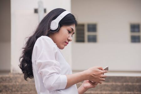 Asian girl student watching media content on smartphones and listening on line with wireless headphones,learn english, online education concept. Banque d'images - 133126239