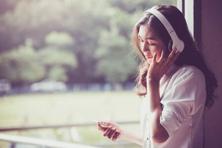 Asian girl student watching media content on smartphones and listening on line with wireless headphones,learn english, online education concept. Banque d'images - 131998487