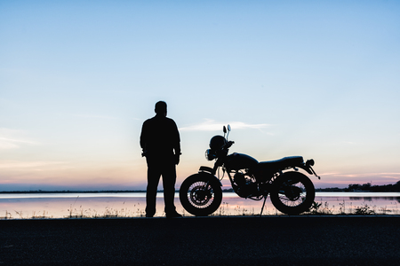 Biker traveler concept,The silhouette of a man standing leisure travelers and  motorcycle on the road along the water during sunset Banque d'images