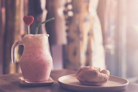 The pink iced milk tea in a glass with a croissant on a wooden table with clothing in the background. In coffee shops and clothing stores, a morning moments. Banque d'images