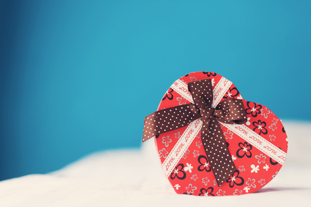 Red heart gift box on white bed and blue wall background