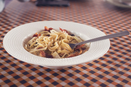 The spaghetti carbonara with a spoon in a dish on the dinner table.