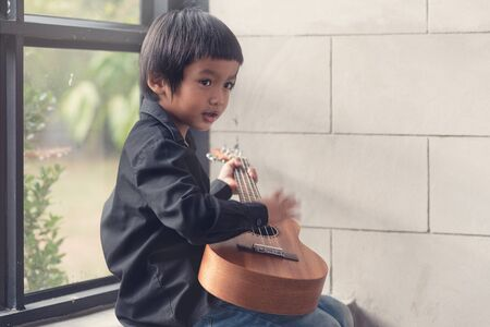 Little Asian boys are happy with playing ukulele.