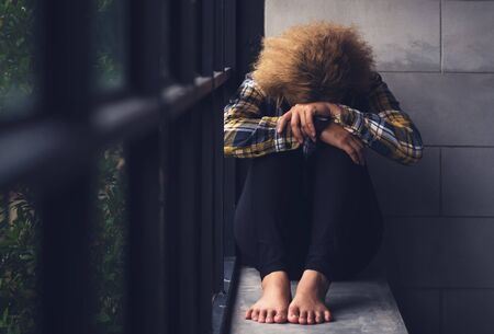 Lonely sad teenager student cry and hug her knees sitting in the dark corner ,Sad woman Unhappy and stressed student on the campus ,Family problems and education concept Banque d'images
