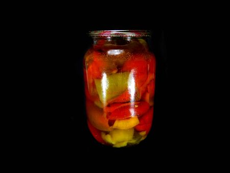 canned peppers isolated on black background