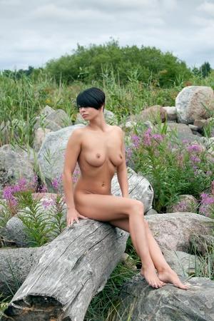 mujer desnuda sentada: Hermosa mujer desnuda sentada en un viejo �rbol contra las piedras y flores de fondo