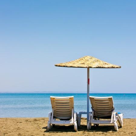 strandstoel: Twee oude strandstoelen en parasol Stockfoto