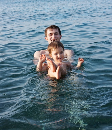 Father teaching his son to swim photo