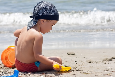 Boy playing with toys on beach photo