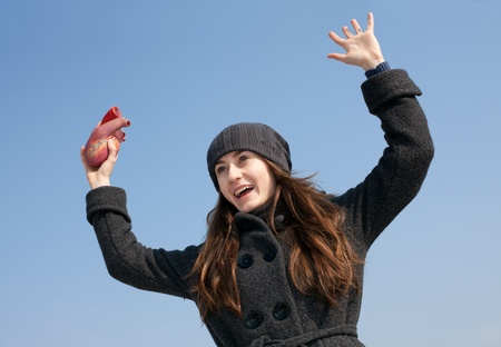 Young woman with a heart in her hand against the blue sky photo