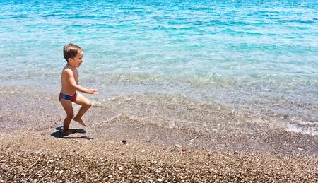 The boy runs on a sea beach photo