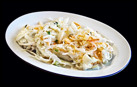Cabbage salad on a plate isolated on black photo
