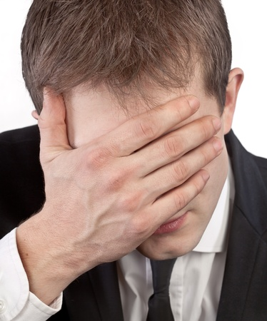 Depressed exhausted businessman covering his face by hand Stock Photo - 12419238