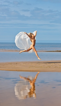 Young nude woman jumping in the sea beach Stock Photo - 12418628