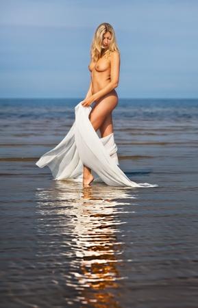 물 반사와 함께 해변에서 누드 젊은 여자