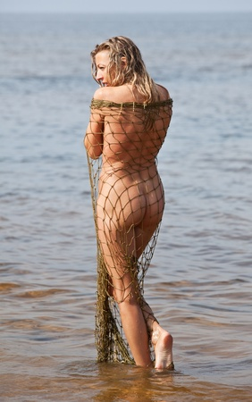 Young naked woman is standing on the beach in the fishing net Stock Photo - 12419232