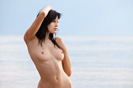 Naked woman standing on sea background Stock Photo