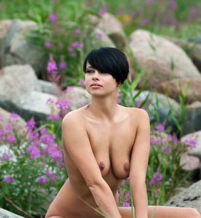 Beautiful nude woman sitting  against stones and flowers background Stock Photo - 12419251