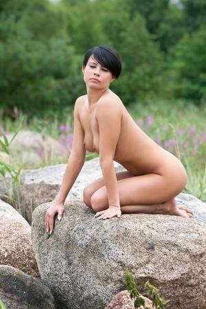 mujer desnuda sentada: Hermosa mujer desnuda sentada sobre la piedra contra la naturaleza de fondo