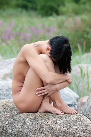 Beautiful nude woman sitting on stone hugging her knees against nature background Stock Photo - 12419262