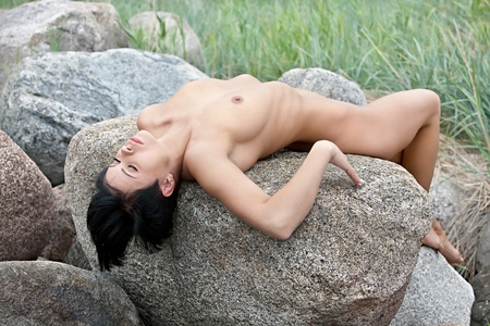 Beautiful nude woman  lies on stones against nature background Stock Photo - 12419266